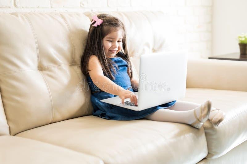 Nätt liten flicka som använder en bärbar dator på soffan royaltyfria foton