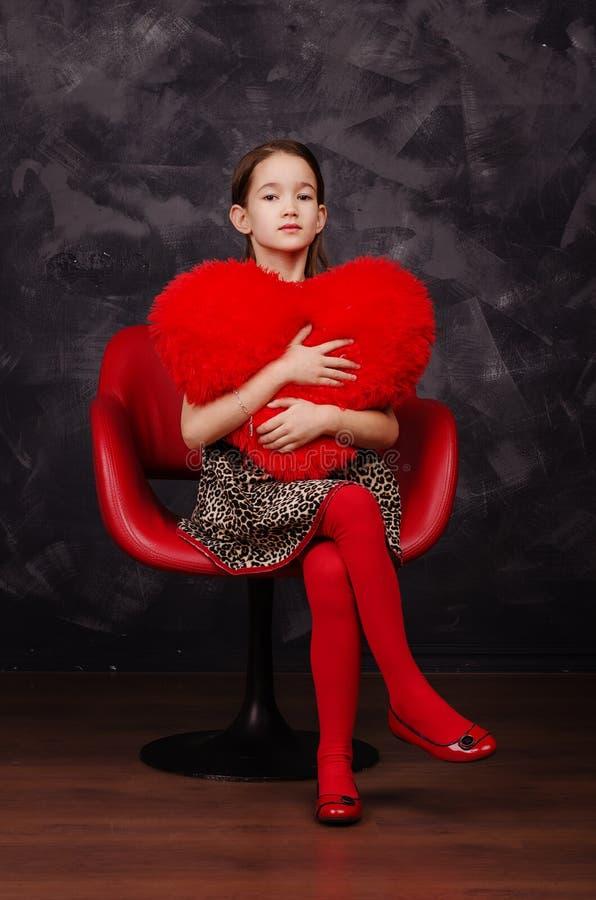 Nätt liten flicka som bär härligt klänningsammanträde i röd fåtölj Hon är hållande flott hjärta i händer härlig för studiokvinna  royaltyfria foton