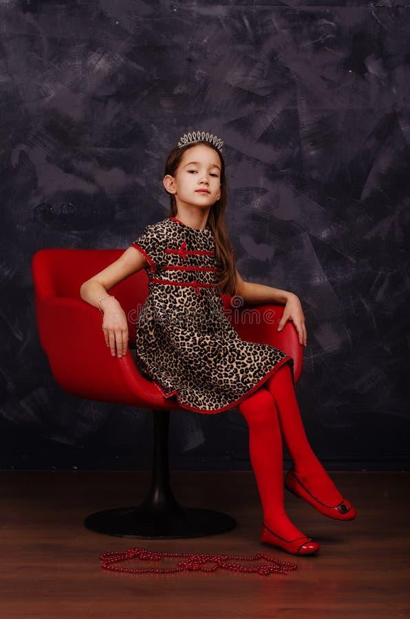 Nätt liten flicka som bär härligt klänningsammanträde i röd fåtölj Hon bär den röda maskeradkarnevalmaskeringen härlig för studio royaltyfri fotografi