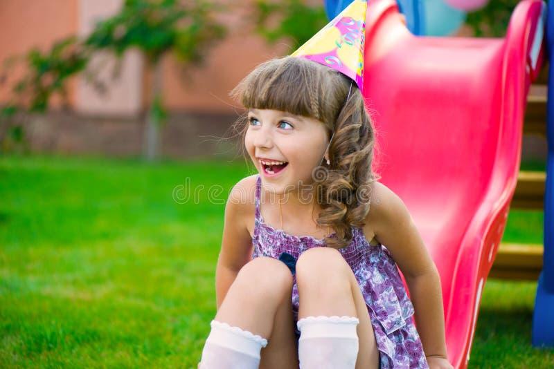 Nätt liten flicka som har gyckel på lekplats royaltyfri bild