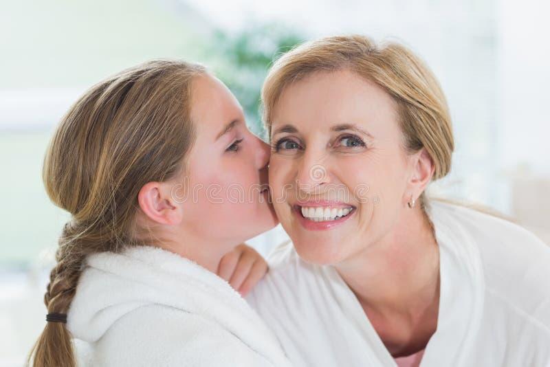 Nätt liten flicka som kysser hennes moder på kind royaltyfri fotografi