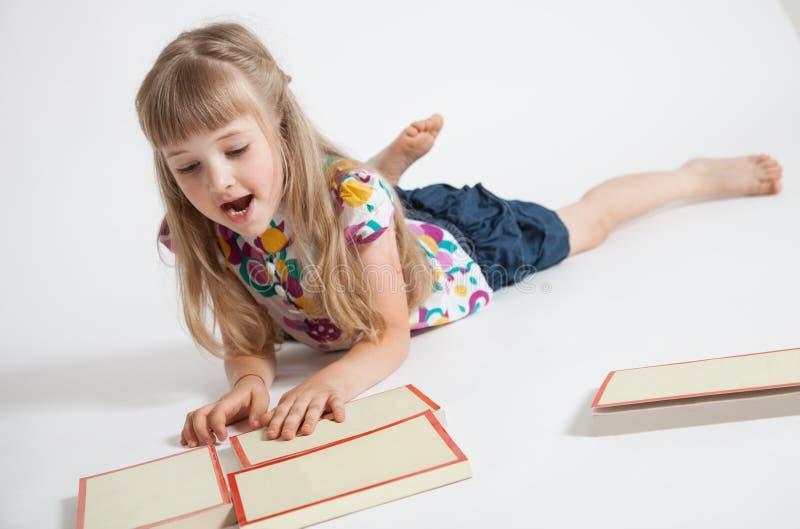 Nätt liten flicka som läser en bok royaltyfri fotografi