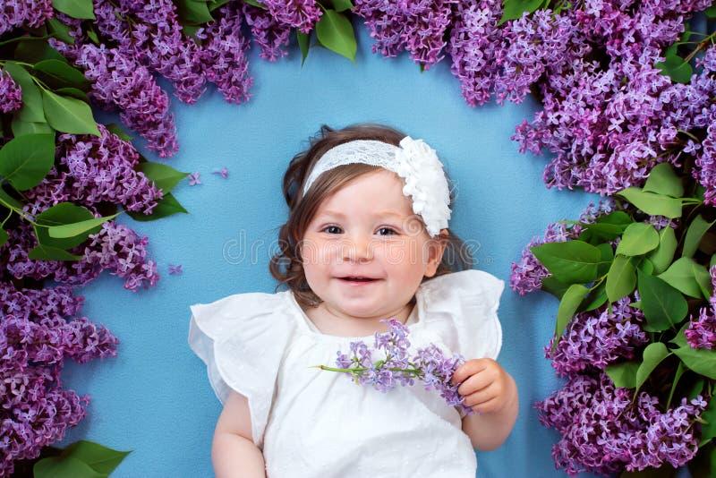 Nätt liten flicka som ligger på blå bakgrund med lila blommor royaltyfri bild