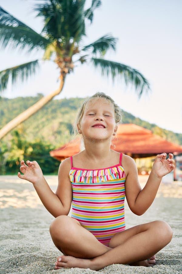 Nätt liten flicka som mediterar i Lotus Pose på den sandiga stranden i sommarsemester royaltyfri fotografi