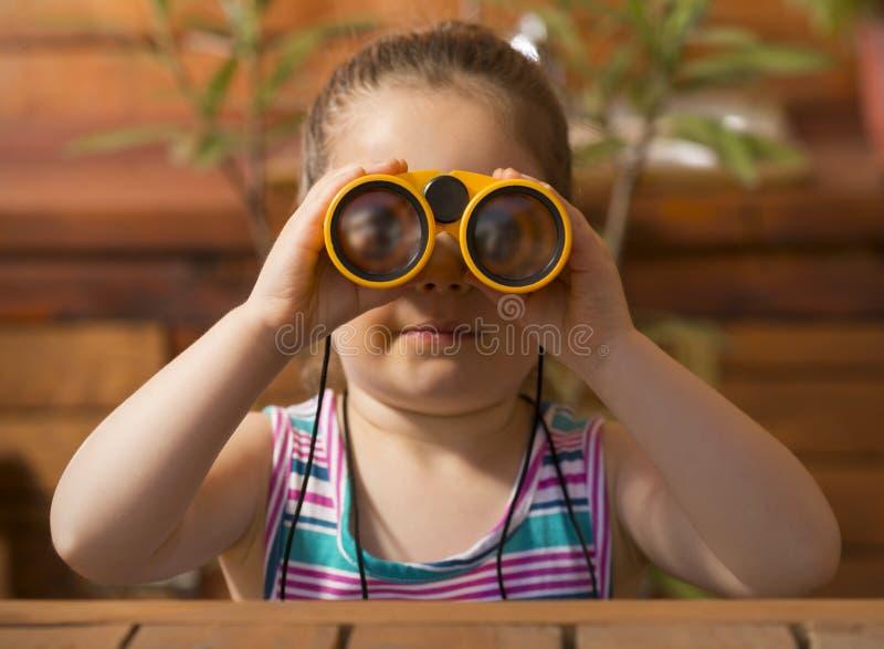 Nätt liten flicka som spelar med kikare royaltyfri fotografi