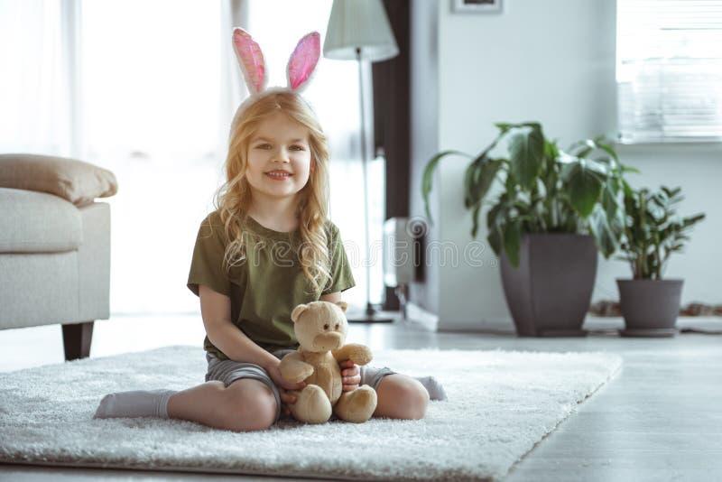 Nätt liten flicka som spelar med leksaken i lägenhet arkivfoto