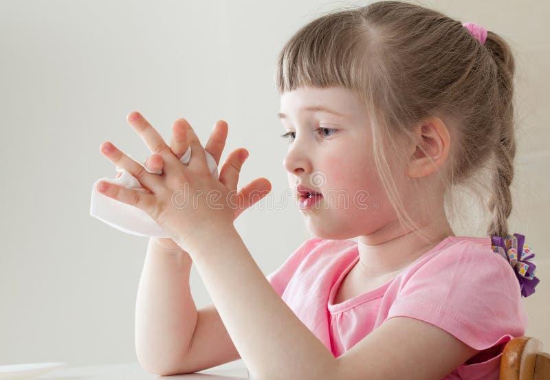 Nätt liten flicka som torkar hennes händer med en vissue arkivbilder