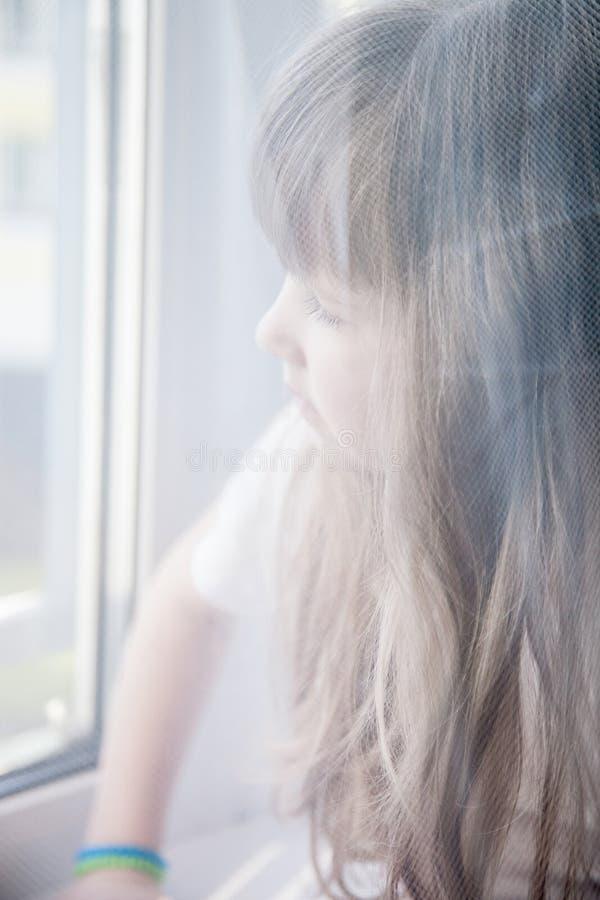 Nätt liten flicka som ut ser fönstret royaltyfria foton