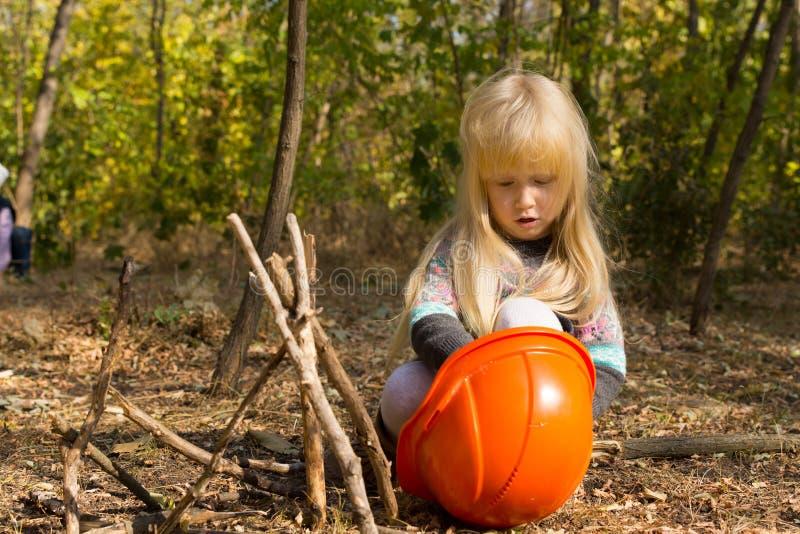 Nätt liten flicka som utomhus spelar med en hardhat arkivfoto