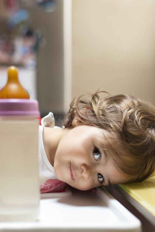 Nätt liten flicka som vilar på en tabell arkivfoto