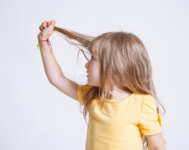 Nätt liten flicka som visar hennes härliga långa hår fotografering för bildbyråer