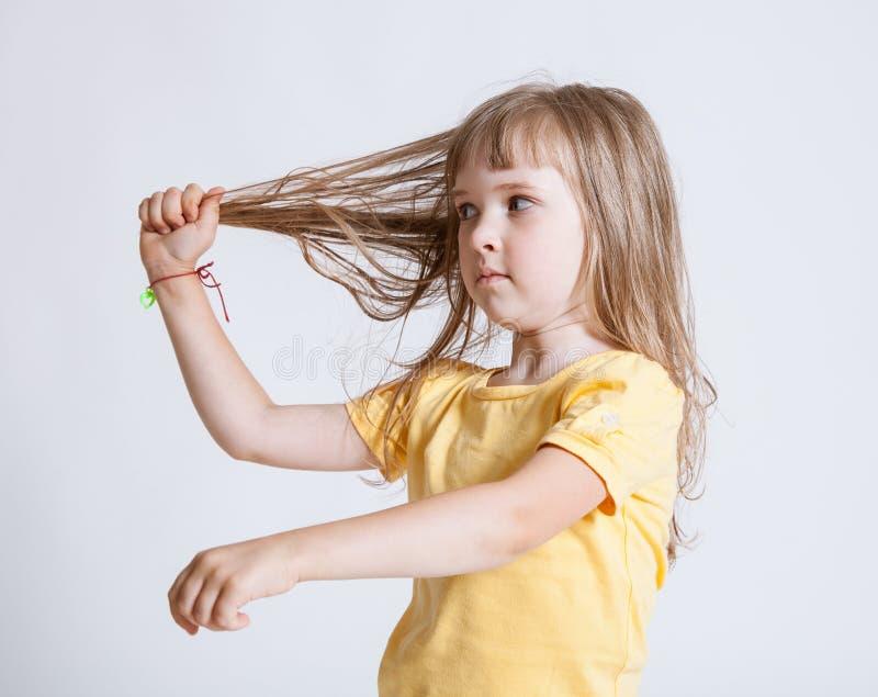 Nätt liten flicka som visar hennes härliga långa hår arkivfoto