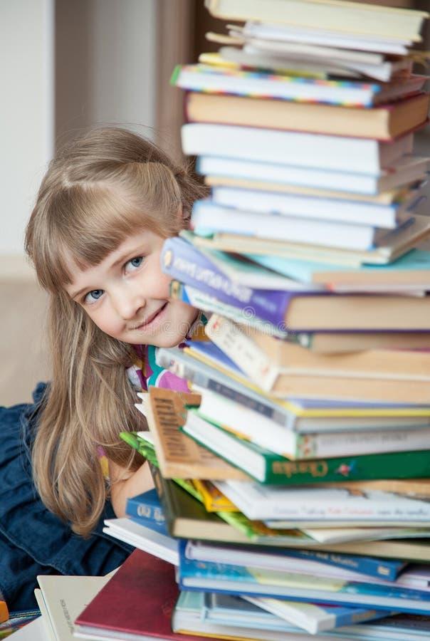 Nätt liten flickanederlag bak en bunt av böcker royaltyfri bild