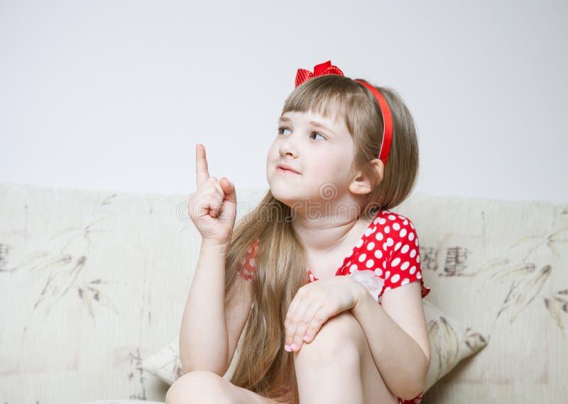 Nätt liten flickasammanträde på golvet och indikera något arkivfoton