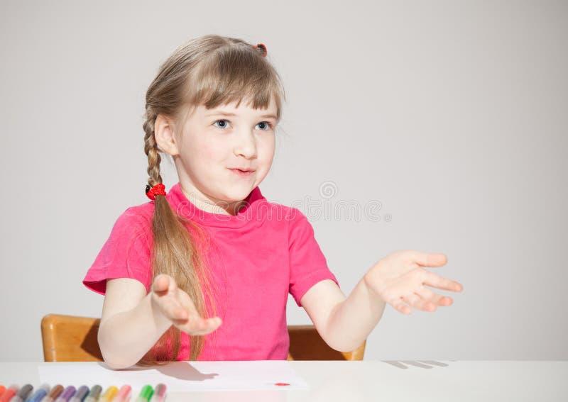 Nätt liten flickasammanträde på tabellen och visningen hennes tomma PA royaltyfria bilder