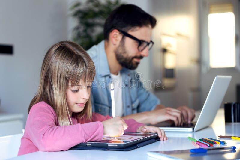 Nätt liten flickateckning på hennes digitala minnestavla medan hennes fader som hemma arbetar med bärbara datorn fotografering för bildbyråer