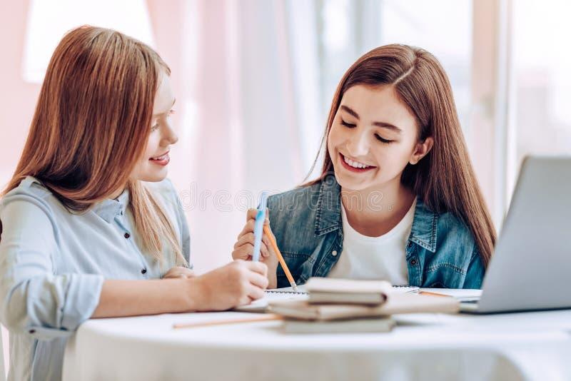 Nätt longhaired flicka som lyssnar till hennes klasskompis arkivfoto