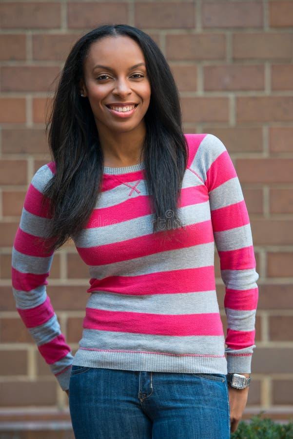 Nätt lycklig afrikansk amerikanhögskolestudentkvinna på universitetsområde royaltyfri foto