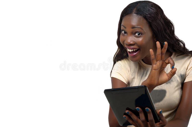 Nätt lycklig afrikansk amerikankvinna genom att använda en minnestavlaPC som visar det ok tecknet.