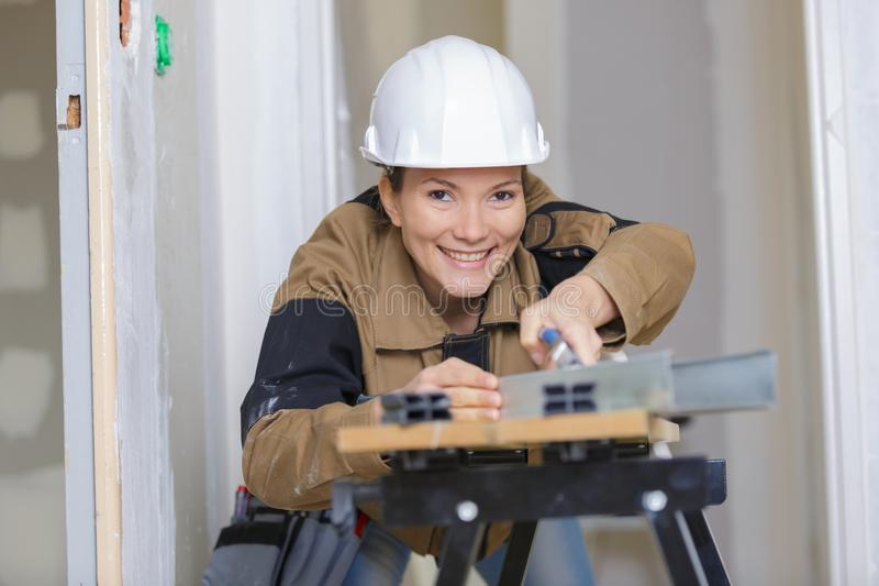 Nätt lycklig kvinnabyggmästare som mäter plankaträ royaltyfri fotografi