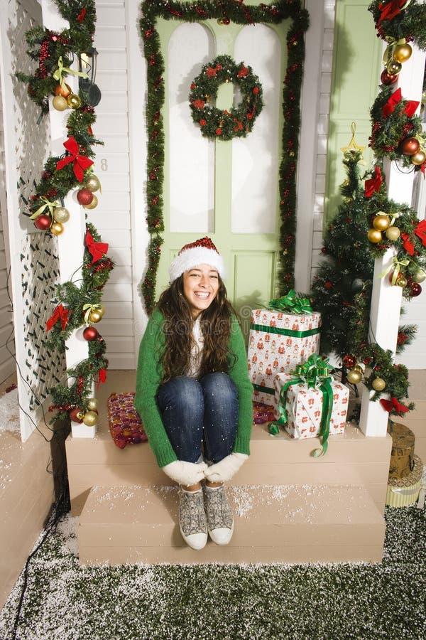 Nätt lycklig le ung tonårs- hipsterflicka i framdel av dekorerat för julhuset, väntande på komma för gäster royaltyfri fotografi