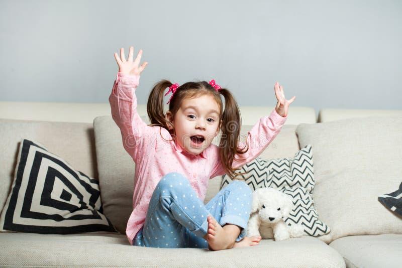 Nätt lycklig liten flicka i tillfälligt bärande sammanträde på soffan med hunden och att le för leksak royaltyfri fotografi