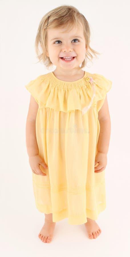 Nätt lycklig litet barnflicka som bär den långa klänningen arkivfoto