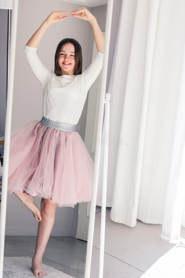 Nätt lycklig tweenflickadans som ballerina som hemma ser spegeln royaltyfria foton