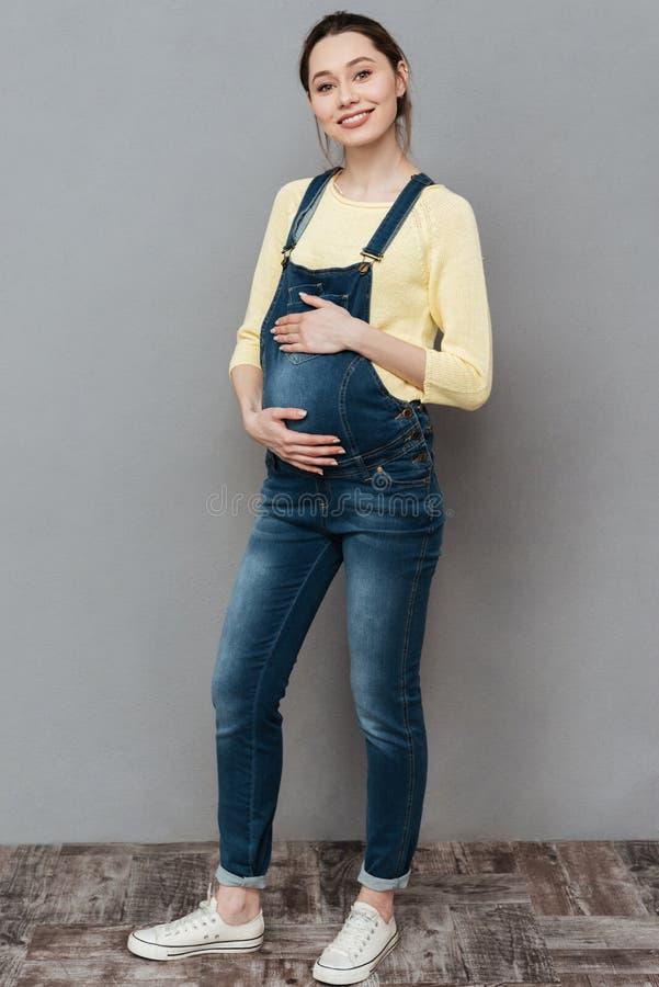 Nätt lyckligt gravid posera för dam arkivbilder