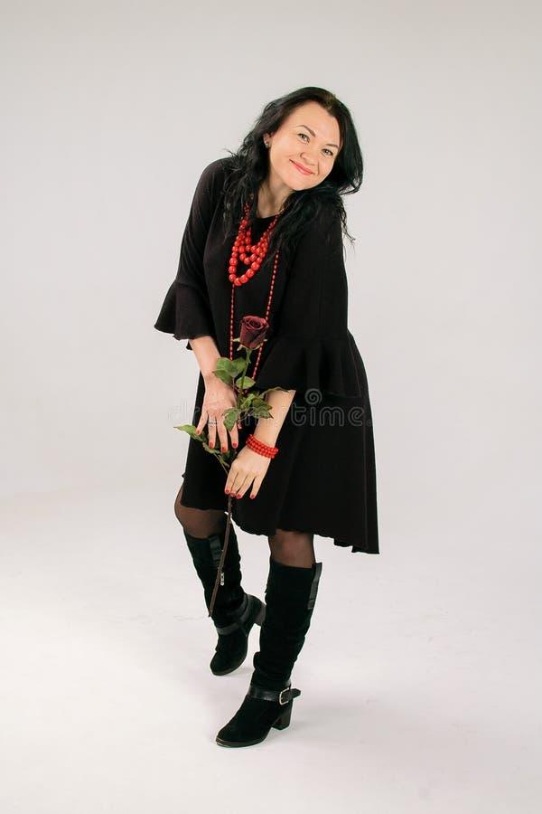 Nätt medelålders kvinna med Rose Dancing i studio i svart klänning och röd halsband fotografering för bildbyråer