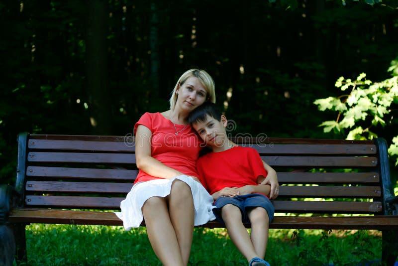 Nätt moder och trevligt sonsammanträde på en bänk royaltyfria foton