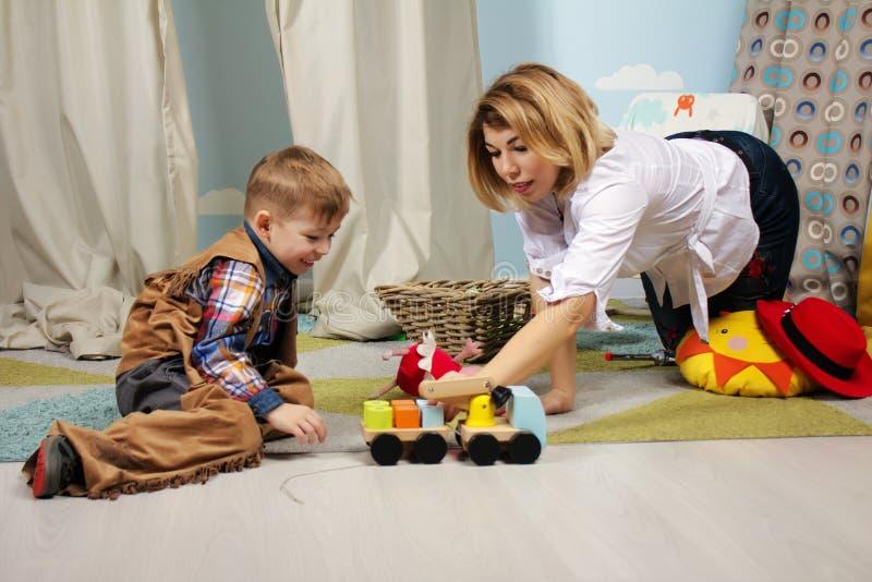 Nätt moder- och ungepojke som tillsammans inomhus spelar royaltyfri fotografi