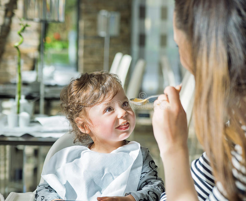 Nätt moder som matar hennes älskvärda barn royaltyfri fotografi