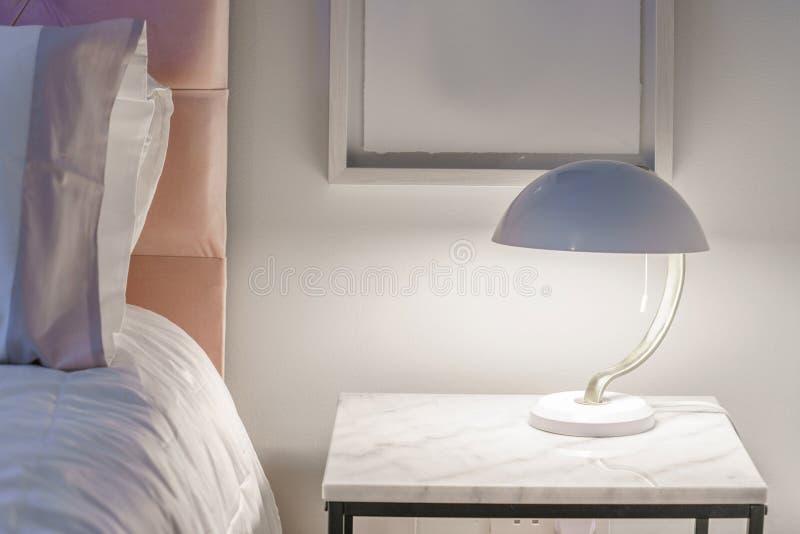 Nätt modernt nattljus på en liten tabell arkivbilder