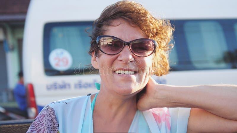 Nätt mogen kvinna i åldrig bärande solglasögon som tycker om sommarsolen Lycklig le kvinna som har gyckel på vindresande in arkivfoto