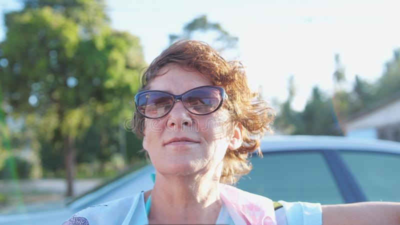 Nätt mogen kvinna i åldrigt i solglasögon som tycker om sommarsolen Lycklig le kvinna som har gyckel på vindresande i öppet arkivbilder