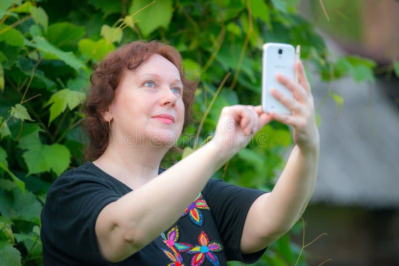 Nätt mogen kvinna som utomhus tar selfie arkivfoto