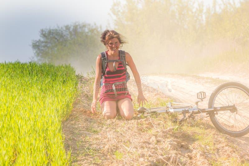 Nätt nedgång för flicka precis av cykelcykeln nära vetefältet på solstrålar Cykeln ligger på jordningen royaltyfria foton