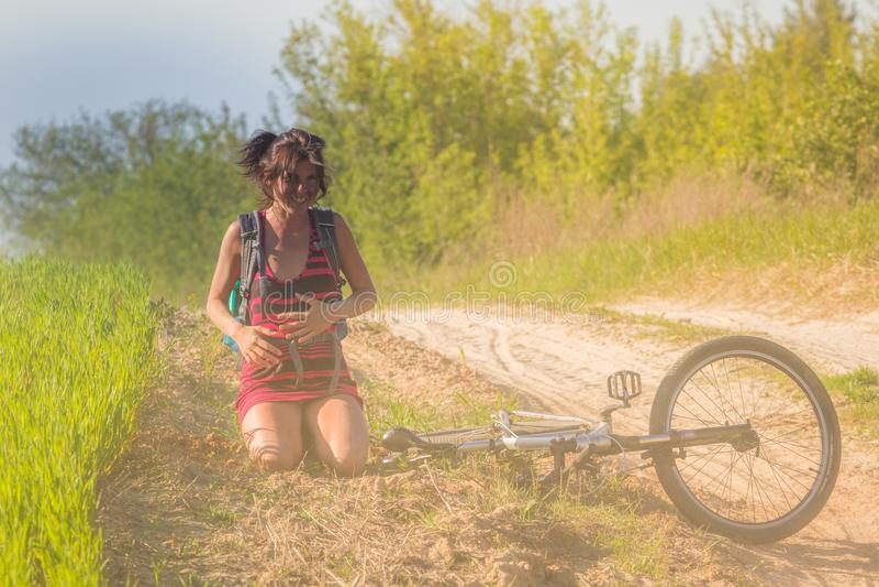 Nätt nedgång för flicka precis av cykelcykeln nära vetefältet på solstrålar Cykeln ligger på jordningen arkivbild