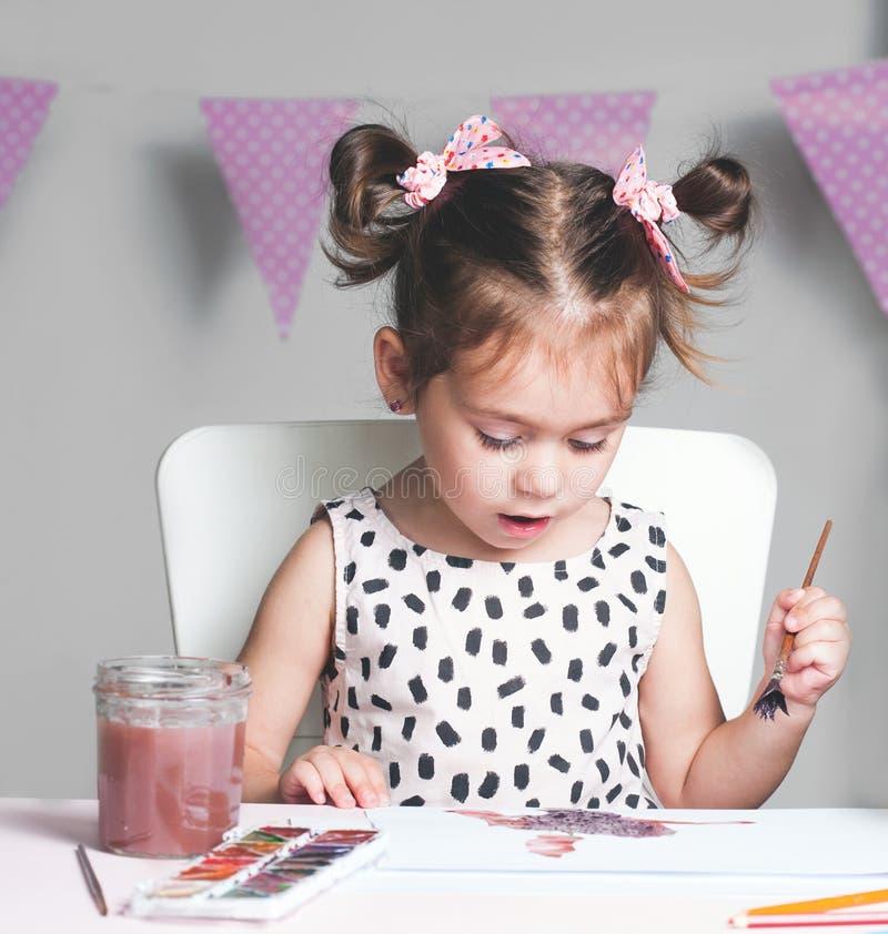 Nätt och gullig liten flickamålningbild med vattenfärgen i studio Begrepp av utbildningsprocessen royaltyfria bilder