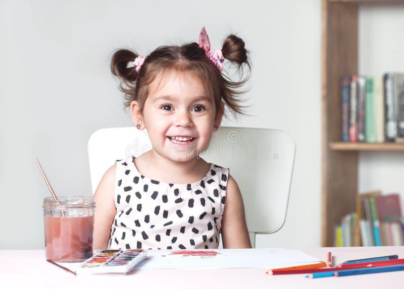 Nätt och gullig liten flickamålningbild med vattenfärgen i studio Begrepp av utbildningsprocessen arkivbilder