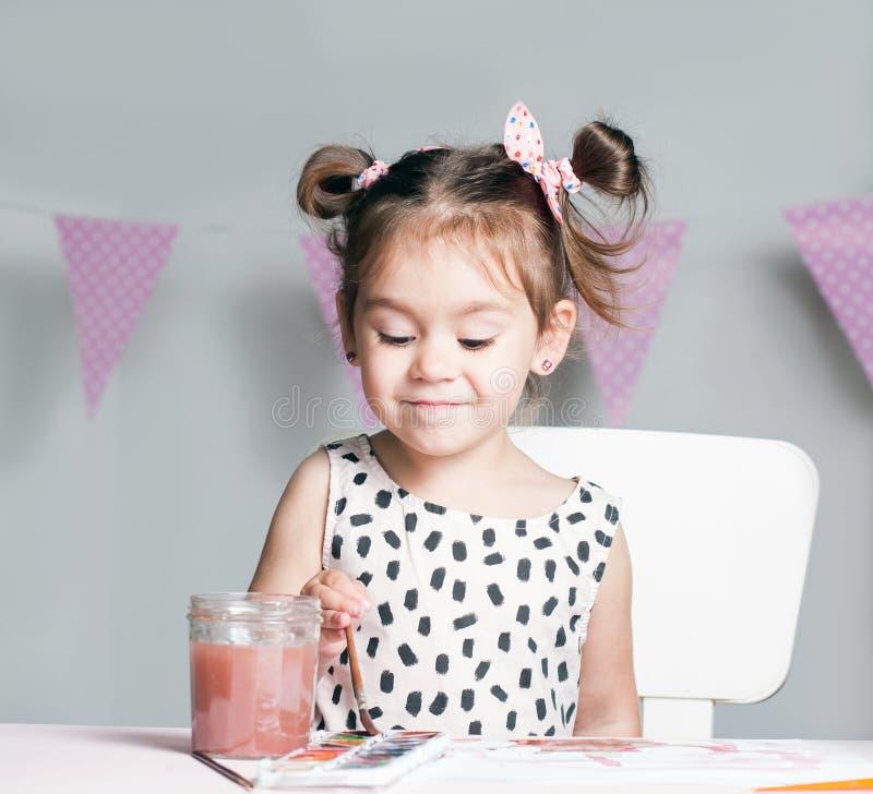 Nätt och gullig liten flickamålningbild med vattenfärgen i studio Begrepp av utbildningsprocessen arkivbild