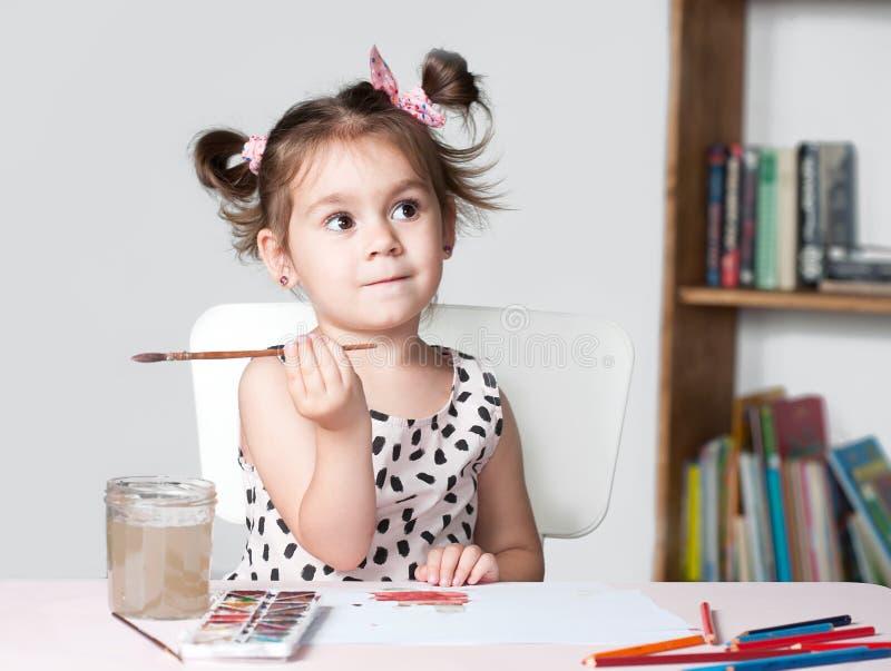 Nätt och gullig liten flickamålningbild med vattenfärgen i studio Begrepp av utbildningsprocessen arkivfoton