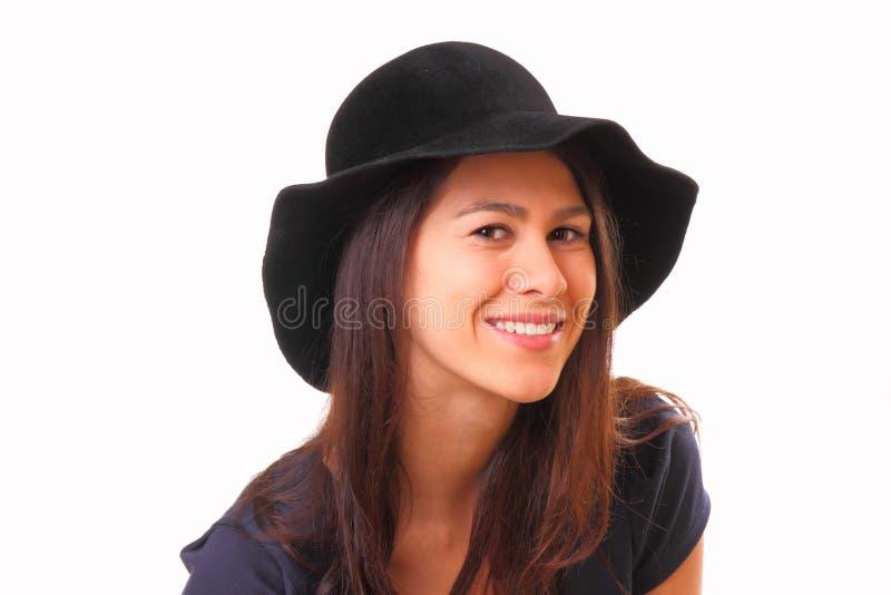 Nätt och le ung kvinna i en svart hatt royaltyfri fotografi