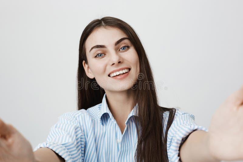 Nätt och slank caucasian kvinna som lyckligt ler, medan sträcka händer in mot kamera som, om rymma den och att stå över arkivfoto
