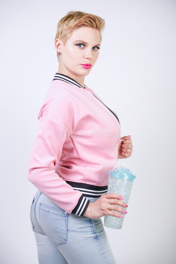 Nätt plus kvinna för kort hår för format med den blåa koppen av vatten omslag och jeans för sport för blond vuxen flicka som bära arkivfoto