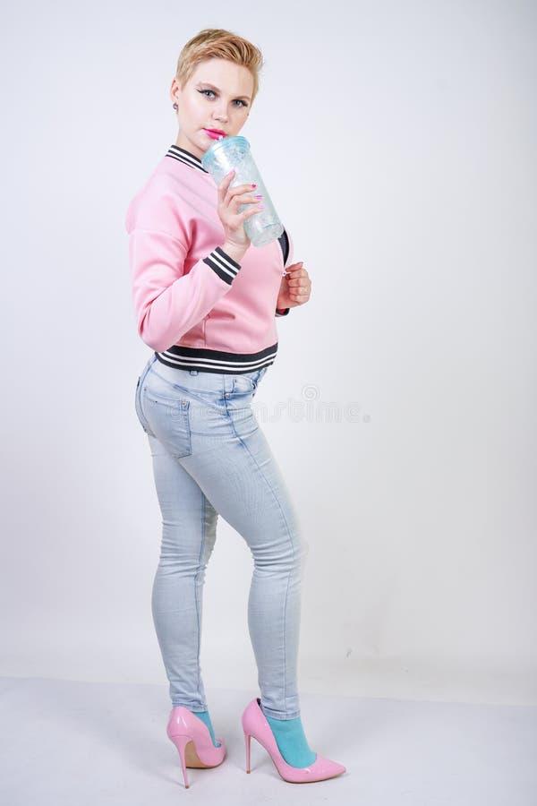 Nätt plus kvinna för kort hår för format med den blåa koppen av vatten omslag och jeans för sport för blond vuxen flicka som bära royaltyfri fotografi