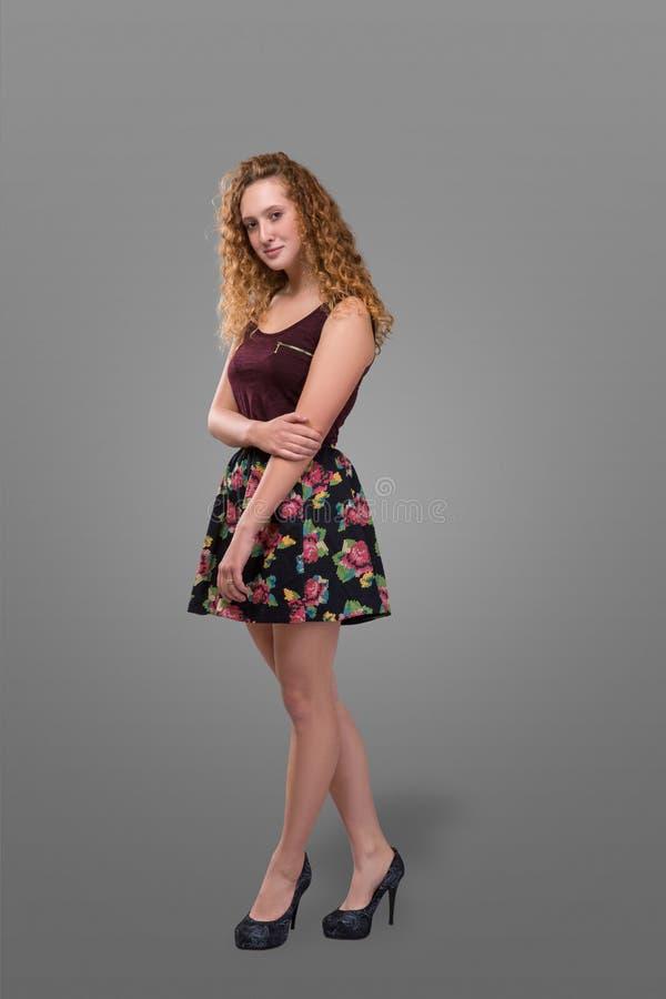 Nätt plus ung rödhårig man för format och lockig-haired flickan som bär den korta kjolen med det blom- trycket över grå bakgrund  royaltyfri bild