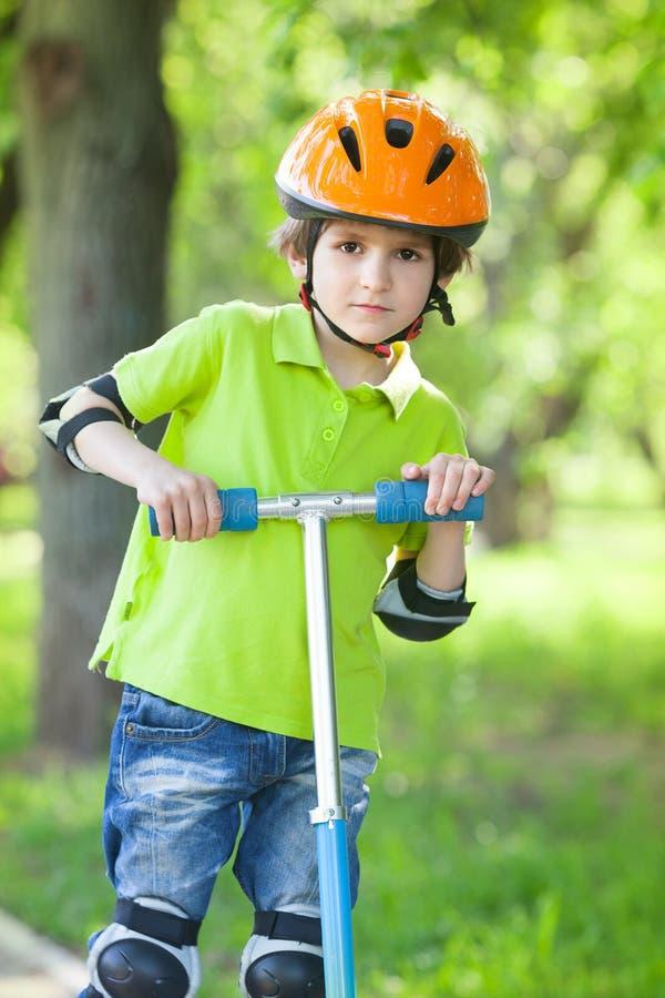 Nätt pojke med sparksparkcykeln royaltyfri fotografi