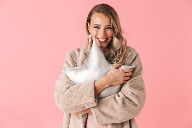 Nätt posera för kvinna som isoleras över den rosa stjärnan för kudde för väggbakgrundsinnehav royaltyfri foto